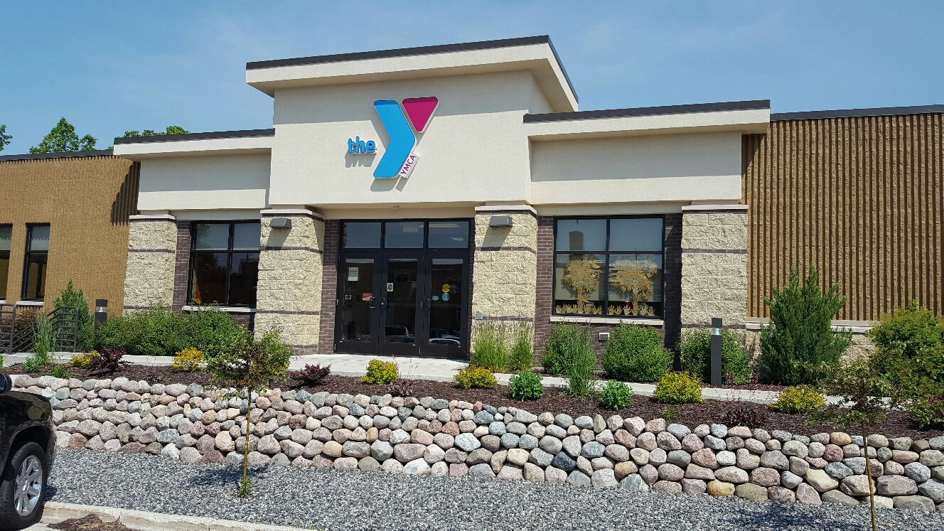 YMCA personal trainer helping man with fitness equipment