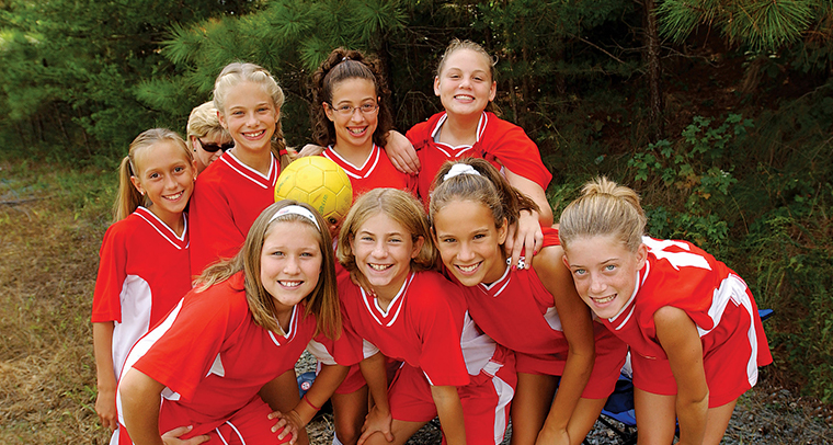 Group of smiling girls posing in red soccer uniforms