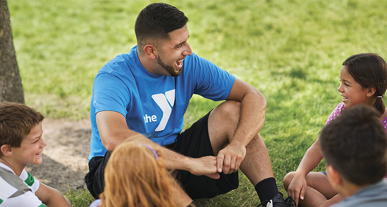 YMCA staff member sitting outside and laughing with a group of children