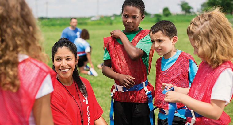YMCA coach talking to a group of children during flag football game outside