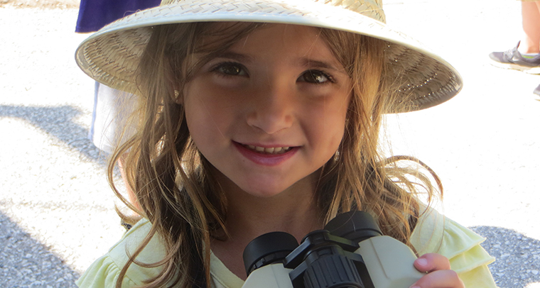 Smiling girl wearing a hat and holding binoculars
