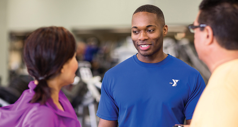 YMCA staff member talking with man and woman in fitness center