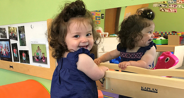 Smiling toddler in YMCA child care center