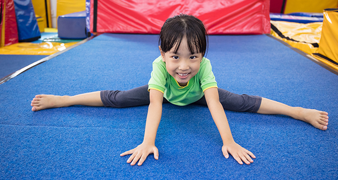 Smiling, young girl playing on gymnastics mat