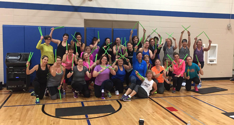 Large group of women holding green drum sticks in YMCA gym
