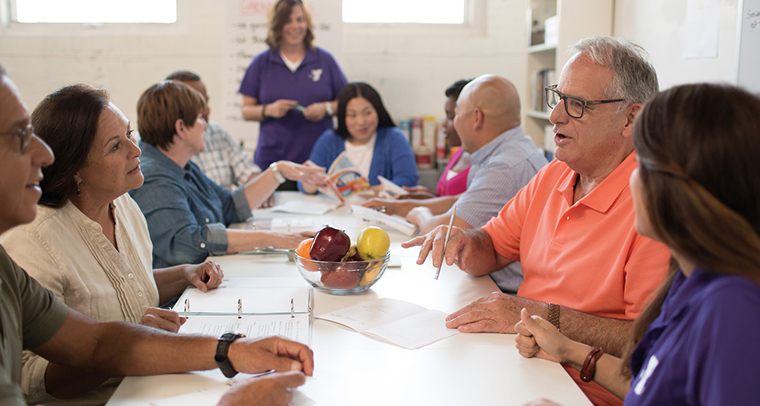 Group of adults discussing diabetes program information while sitting at a table