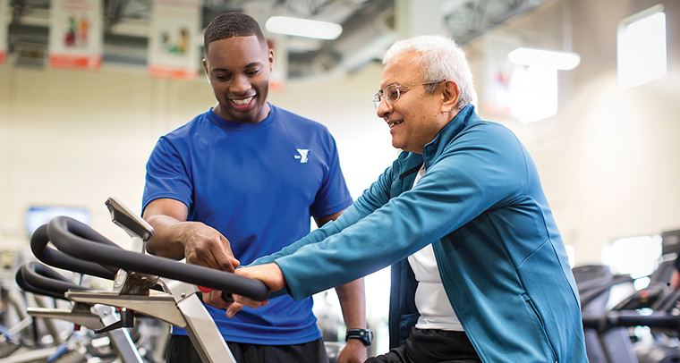 YMCA staff member teaching middle-aged man how to use stationary bicycle in fitness center