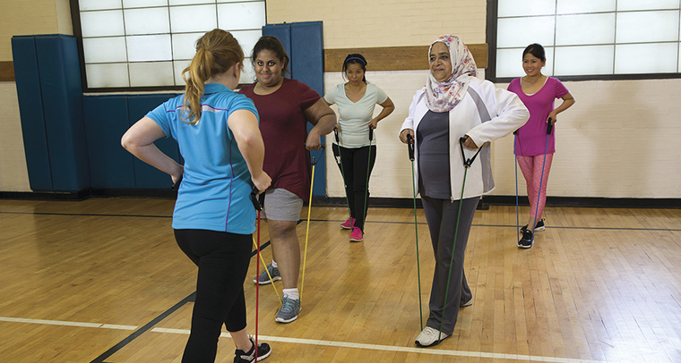 Female instructor teaching women resistance band stretches in YMCA gym