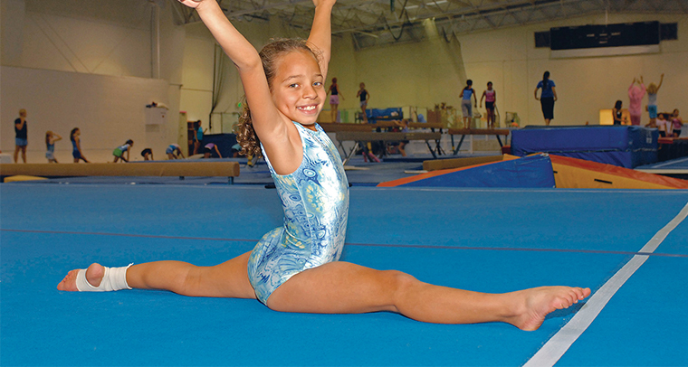 Young girl in leotard doing the splits in YMCA gymnastics center