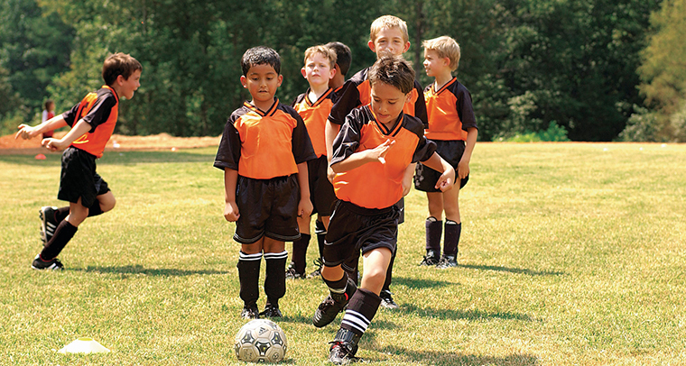 Young boys in orange and black uniforms lining up to kick soccer ball outdoors