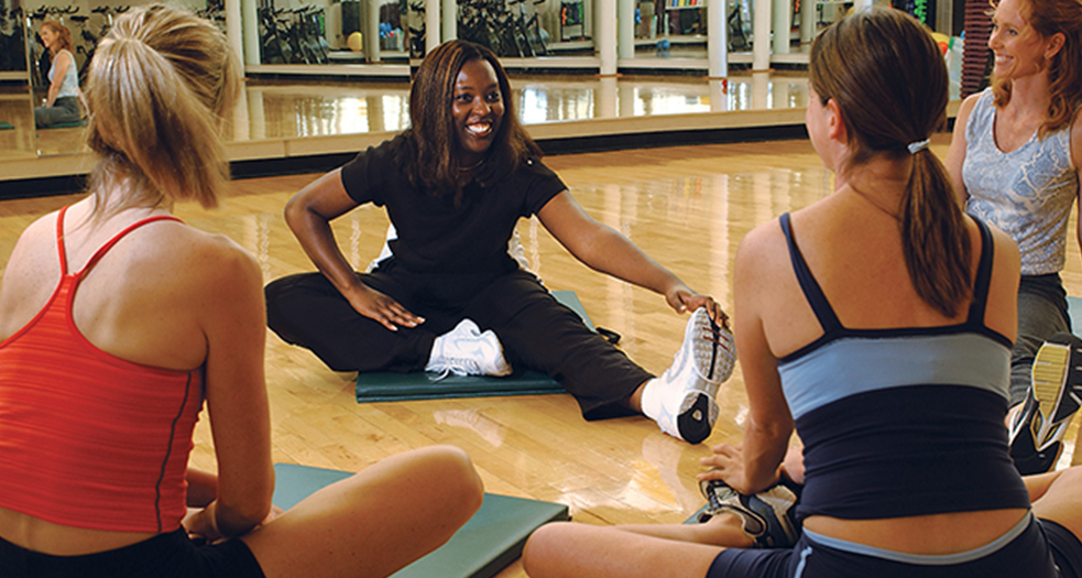 Young woman sitting with a group of women doing stretches