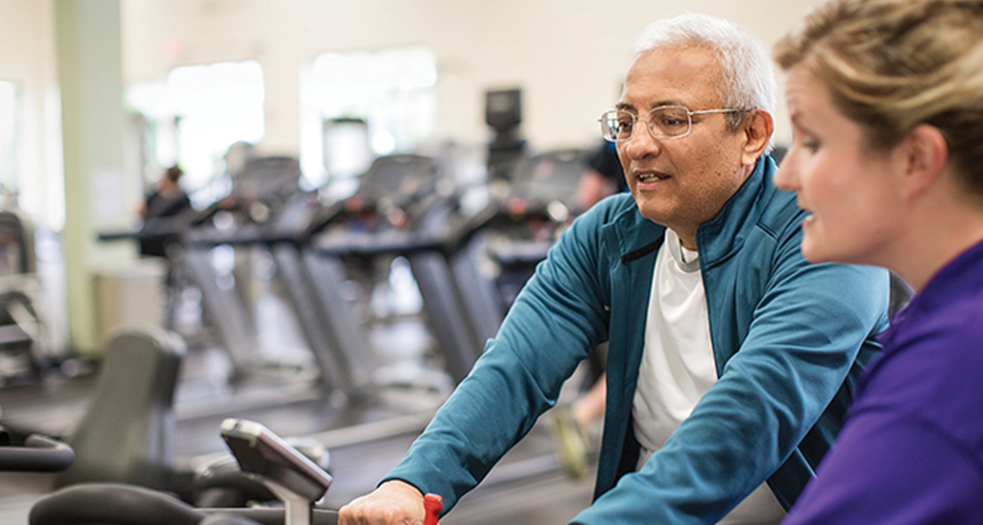 Female instructor showing middle-aged man how to use stationary bicycle in fitness center