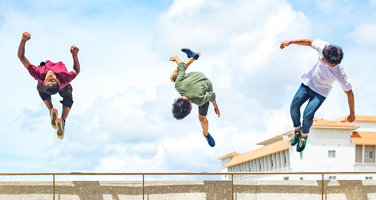 Three teen boys doing back flips