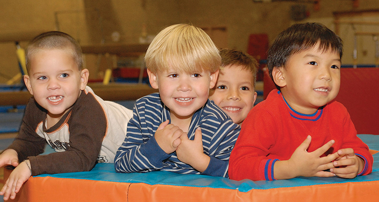 Group of young boys smiling in YMCA play area