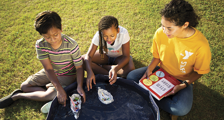 YMCA staff member sitting outside with two kids doing a science project