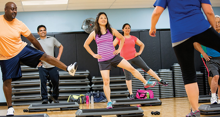 Group of men and women in fitness class balancing on one leg