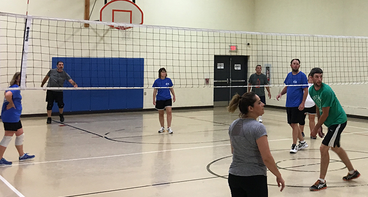 Men and women in fitness attire playing volleyball in YMCA gym