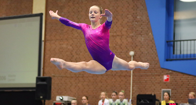 Girl in pink and purple leotard leaping in gymnastics competition