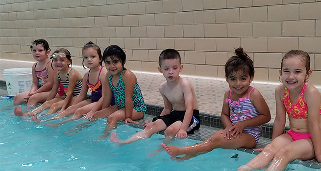 Group of kids in swimming suits sitting on the edge of an indoor pool