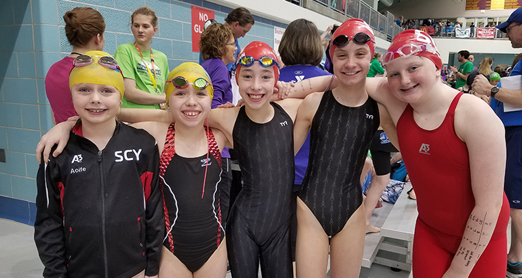 Smiling group of kids in swim suits wearing bathing caps and goggles