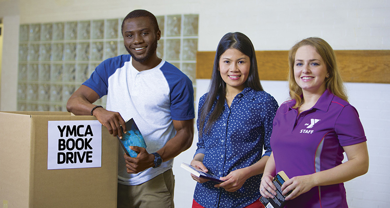 Three young adults volunteering at YMCA book drive