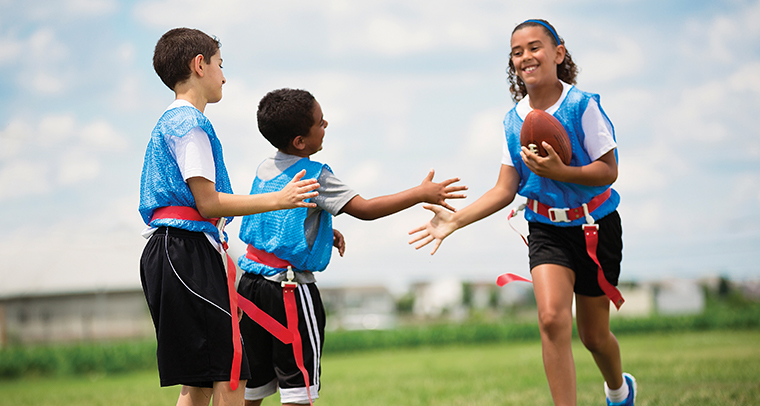 Kids in jerseys giving high fives after a flag football game outside