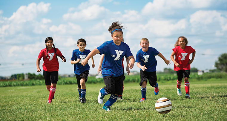 Boys and girls in uniform running after soccer ball in field